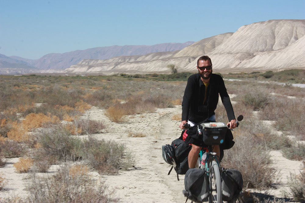 Hubert pozuje na rowerze, w tle góry