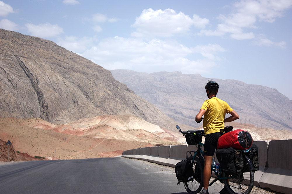 Mężczyzna na rowerze, na tle gór Kazachstanu